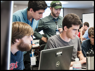 Several interns look at a computer monitor.