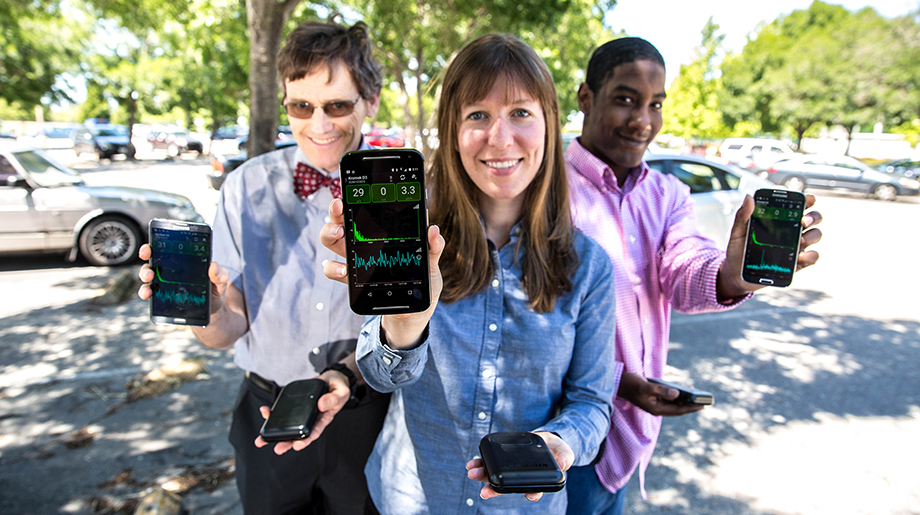 Three scientists hold up phones displaying information from an application.