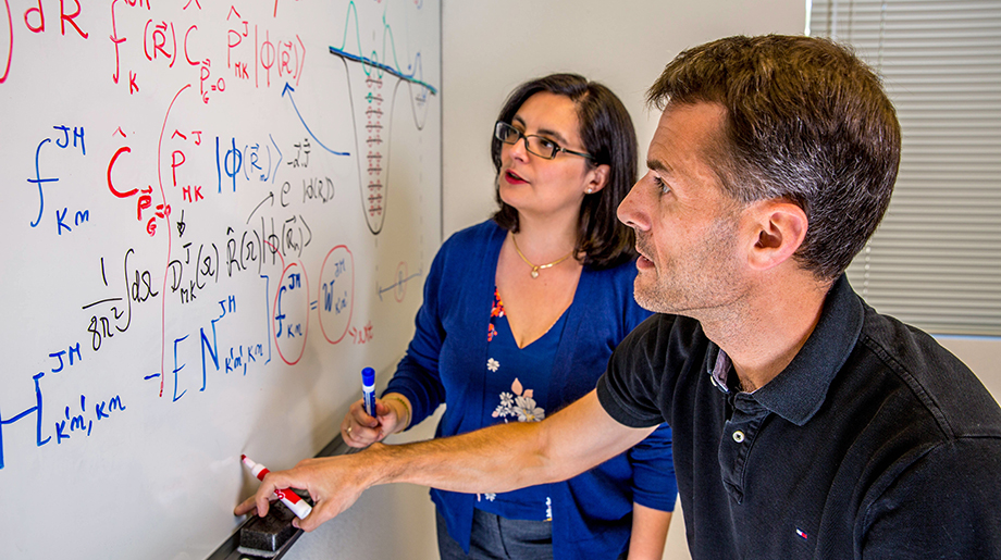 Two scientists study formulas written on a white board.
